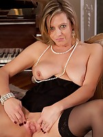 Elegant cougar Louise Pearce naked at the piano.